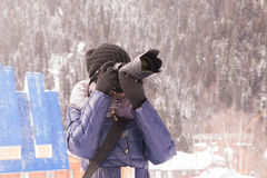 Young girl takes pictures winter mountain landscape in a snow storm on a SLR camera with telephoto lens Royalty Free Stock Images