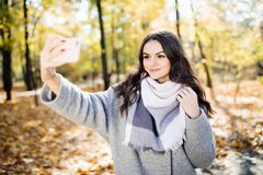 Young girl takes a selfie on the backgroung autumn park. Young girl takes a selfie on the backgroung of a wall with autumn beautiful leaves Royalty Free Stock Photography