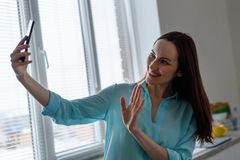 A young girl takes a selfie on the front camera in the interior of the kitchen at home, welcomes open hand Stock Photo