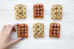 Young girl takes vegan toast with fruits, seeds, peanut butter over white wooden background, top view. Dieting concept. stock photos
