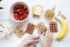 Young girl takes vegan toast with fruits, seeds, peanut butter over white wooden background, top view. Healthy breakfast with ingr stock photography