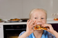 Young girl taking a bite of homemade pizza Royalty Free Stock Photos