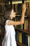 Young girl taking book from shelf in old library. Stock Image
