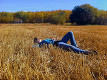 A young girl taking a break while working on a farm, laying down in a straw field looking up at the sky Royalty Free Stock Photography