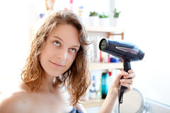 Young girl taking care of her hairs in a bathroom Royalty Free Stock Photos