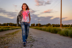 Young girl taking an evening walk in the country Royalty Free Stock Photos