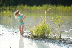 Young girl taking healing mud baths on lake Gela near Vilnius, Lithuania. Child having fun with mud. Kid playing with medicinal clay stock photos
