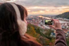 Young girl taking a photo of Heidelberg from the hill royalty free stock photography