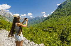 Young girl taking photo of mountains landscape Royalty Free Stock Image