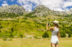 Young girl taking photo of mountains landscape Royalty Free Stock Photo