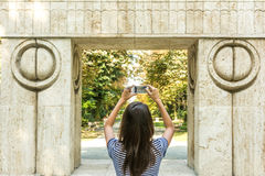 Young Girl Taking Photography Of The Gate of the Kiss. Stone Sculpture Made By Constantin Brancusi in 1938 In Targu Jiu, Romania Royalty Free Stock Photos