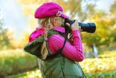 Young girl taking photos in autumn park Stock Image