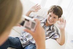 Young girl taking picture of smiling young boy Stock Photo