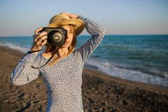 Young girl taking pictures at the beach stock photo
