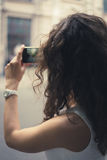 Young girl taking pictures on a phone. A young girl taking pictures on a smart phone. The girl dressed in a white sleeveless dress. She has curly brown hair Royalty Free Stock Photography