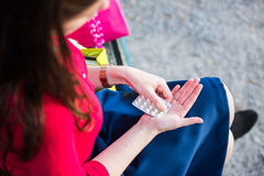 Young girl is taking a pill in the park. Girl dressed in red is taking a pill in the park on a bench royalty free stock images