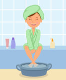 Young girl taking Spa treatments. Female in the bathrobe keeps feet in hot water before a pedicure. Royalty Free Stock Images