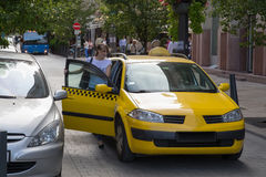 The young girl is taking a taxi. The young girl calculated with a taxi. Yellow taxis. Stock Photos