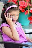 Young girl talking on the cell phone. A cute little 8 year old girl talking on a cell phone, Shallow depth of field Royalty Free Stock Photography