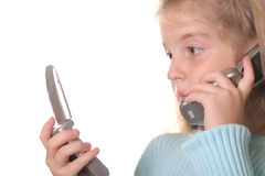 Young girl talking on a cell phone looking at anot. Shot of a young girl talking on a cell phone looking at another phone Royalty Free Stock Photo