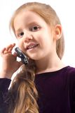 Young girl with talking on cell phone and smiling. Portrait of friendly child with long gorgeous red hair calling with mobile phone and smiling. Great Stock Image