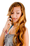 Young girl talking on cellphone. Young girl looking downward while talking on cellphone Royalty Free Stock Photography