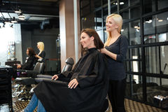 Young girl talking with hairdresser in beauty salon royalty free stock image
