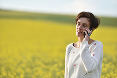 Young girl talking on iphone in a canola field Royalty Free Stock Image