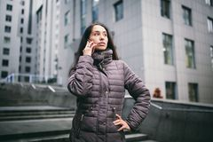 Young girl talking on mobile phone in courtyard business center. girl with long dark hair dressed in winter jacket in royalty free stock photo