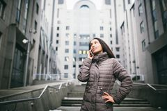 Young girl talking on mobile phone in courtyard business center. girl with long dark hair dressed in winter jacket in cold weather Stock Photos
