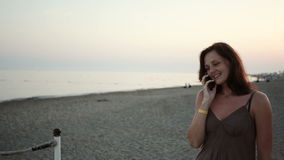 Young girl talking on the phone at the beach stock footage