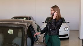 A young girl talking on the phone in the showroom, she asks to buy a new car. A young girl talking on the phone with her husband or parents in the showroom of stock footage