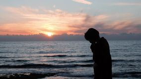 Young girl talking on phone at rocky shore. Silhouette of girl talking on phone against sea sunset. Attractive woman smiles and ta stock video