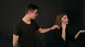 A young girl is talking on the phone, she is ignoring the guy and he is angry. A young girl is talking on the phone while standing next to her boyfriend, she is stock video footage