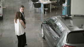 Young girl talking with salesman in car showroom. Pretty girl with salesman in suit are standing near the modern automobile in car dealership. Smart seller tells stock video footage