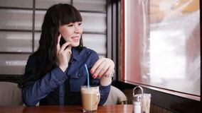 Young girl talking on smartphone in the cafe stock footage