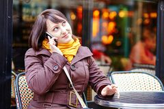 Young girl talking on thephone in Parisian cafe Royalty Free Stock Image