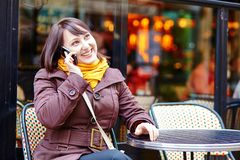 Young girl talking on thephone in Parisian cafe Stock Photos