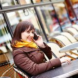 Young girl talking on thephone in Parisian cafe Stock Images