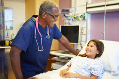 Young Girl Talking To Male Nurse In Hospital Room Stock Photo