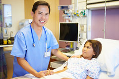 Young Girl Talking To Male Nurse In Hospital Room. Wearing Scrubs And Stethoscope Smiling To Camera Royalty Free Stock Photography