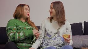 Young girl talks with her fat girlfriend sitting at sofa at home. Young girl in white sweater talks with her fat girlfriend sitting at sofa at home. Pretty stock video
