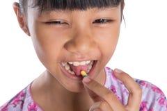 Young Girl Tasting Medicine Pills II Stock Image
