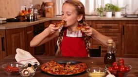 Young girl tasting home made pizza. Young girl tasting some home made pizza, biting from two slices at a time stock video