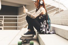Young girl with tattoo and dreadlocks listening to music while sitting on the steps royalty free stock photos