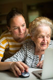 Young girl teaches elderly woman working on the computer. Royalty Free Stock Images