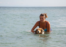 Young girl is teaching dog to swim. Young girl teaching dog to swim in the sea stock image