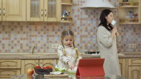 Adorable little girl study to cook salad while her mother talking on phone stock footage