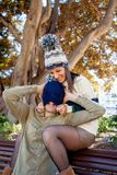 A couple plays with a woolen hat in a public park royalty free stock images