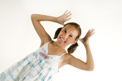 Young girl teasing. Young girl with hands as antlers isolated on a white background Royalty Free Stock Photo